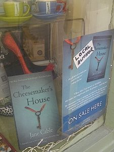 Image of Jane Cable's book 'The Cheesemaker's House' in the window display of gift shop Present Surprise in Chichester