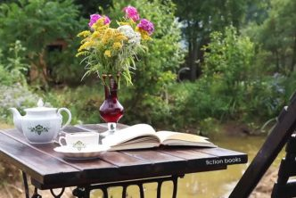 Tea, flowers and an open book on a table in the garden - Used to feature my book reviews